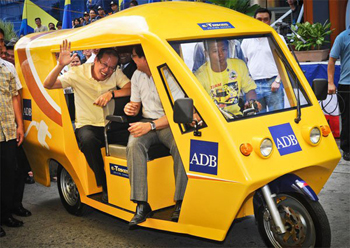 President Aquino waves while onboard a protype e-trike unveiled recently by the Department of Energy and Asian Development Bank. Click on image for source